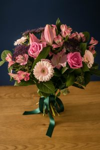 A pretty pink and purple hand-tied bouquet complimenting all shades of these popular colours. We have carefully put together scented Pink Lilies, Pink Roses, Purple Trachelium,and Pink Alstroemeria complemented with seasonal foliage.